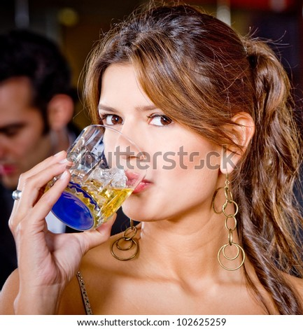 Portrait of a beautiful woman at a party having a drink