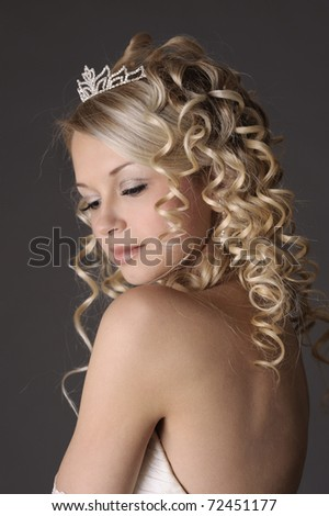 Portrait of a beautiful woman dressed as a bride over gray background. - stock photo