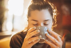 portrait of a beautiful woman drinking coffee or tea with a large mug sitting in a room where a lot of bright sunlight and sunlight go through the windows and create a warm light atmosphere