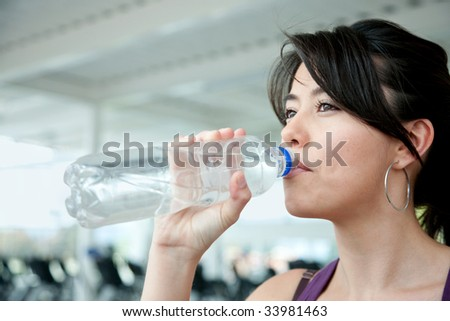 Portrait of a beautiful woman drinking water at the gym
