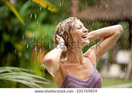 Portrait of a beautiful woman enjoying tropical rain falling on her in an exotic garden.