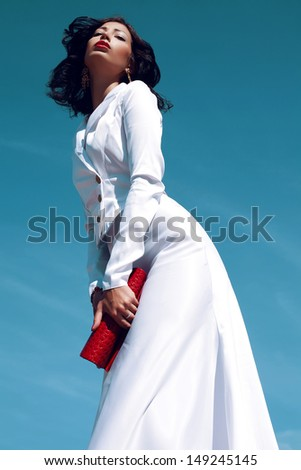 Portrait of a beautiful woman (fashion model) posing in elegant white atlas cocktail dress with red leather clutch in her hands over blue sky background. Sunny & cloudy weather. Outdoor shot