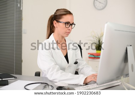 portrait of a beautiful woman female doctor in medical practice office working on computer Foto stock ©