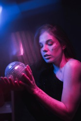 Portrait of a beautiful woman from the 80's dancing in a dark room at a party with a disco ball in her hands in purple and snow light with glare.
