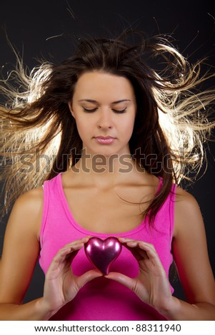 portrait of a beautiful woman holding a heart