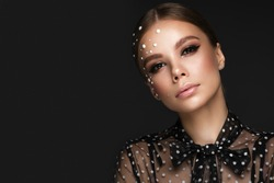 Portrait of a beautiful woman in a black dress with pearls and classic makeup. Beauty face
