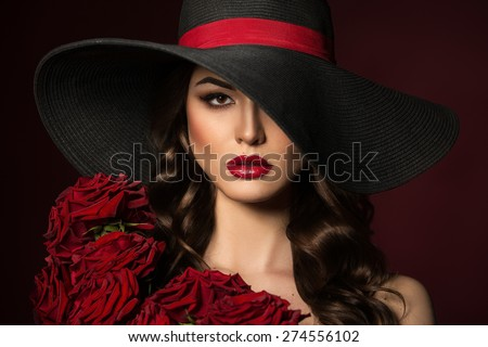 24942f38649 Portrait of a beautiful woman in a black hat with red roses on the  shoulders.