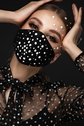 Portrait of a beautiful woman in a black mask with pearls and classic makeup. Mask mode during the covid pandemic.