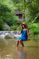Portrait of a beautiful woman in blue dress sitting on a swing, talking on the phone happily in the midst of nature, waterfall and green trees.