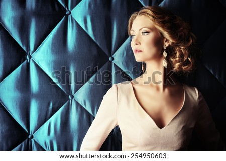 Portrait of a beautiful woman in elegant evening dress posing over vintage background. Jewellery.  Fashion shot. Hairstyle. #254950603