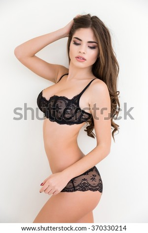 Portrait of a beautiful woman in sexy black lingerie posing isolated on a white background #370330214