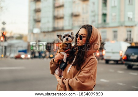 Portrait of a beautiful woman in stylish clothes with a dog in her arms walking around the city with a serious face and hugging a pet. Foto stock ©