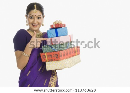Portrait of a beautiful woman in traditional Assamese dress holding gifts and smiling