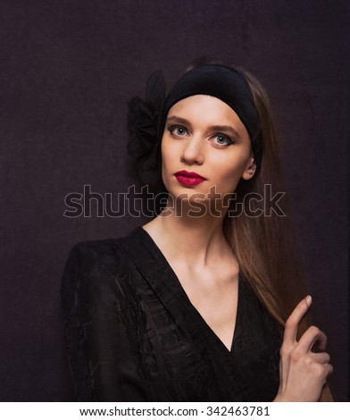 Portrait of a beautiful woman in vintage style over old dark fashioned wall #342463781