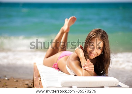 portrait of a beautiful woman on the beach - stock photo