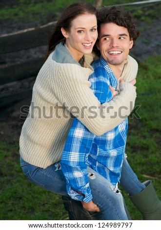Portrait of a beautiful woman piggyback handsome man outdoors