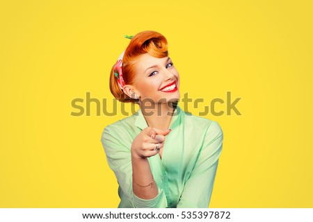 portrait of a beautiful woman pinup retro style pointing at you smiling laughing isolated yellow background wall. Body language, gestures, psychology.