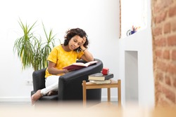 Portrait of a beautiful woman reading a book at home. Space for text.