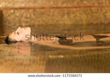 Portrait of a beautiful woman relaxing in a thermal pool