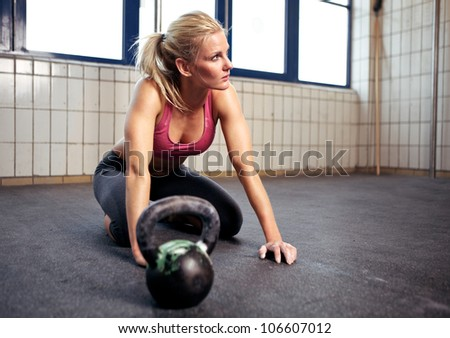 Portrait of a beautiful woman resting during her fitness exercise with a kettlebell