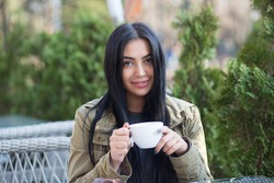 Portrait of a beautiful woman smiling outdoors holding cup of tea outside on a terrace of a trendy cafe coffee shop
