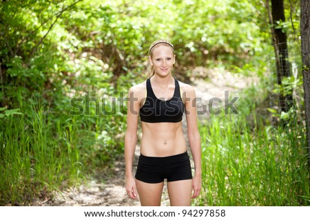 Portrait of a beautiful woman standing in sportswear against blur background