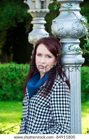 portrait of a beautiful woman standing in the park near vintage column