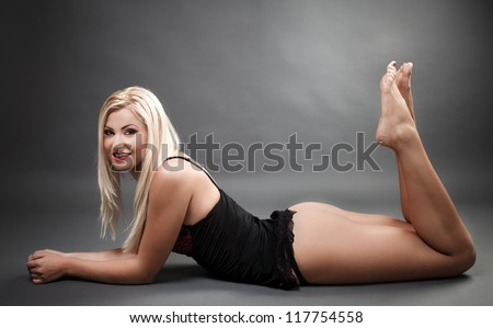 Portrait of a beautiful woman wearing lingerie while laying on the floor