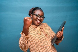 Portrait of a beautiful woman wearing spectacles,holding a file and feeling successful,winning,celebrating isolated on a blue studio background
