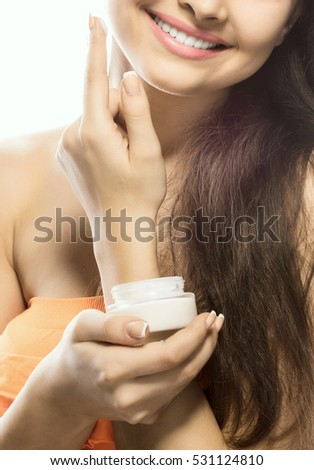 portrait of a beautiful woman who anoints the person holding a cream jar with cream and smiling. Isolated white background.
