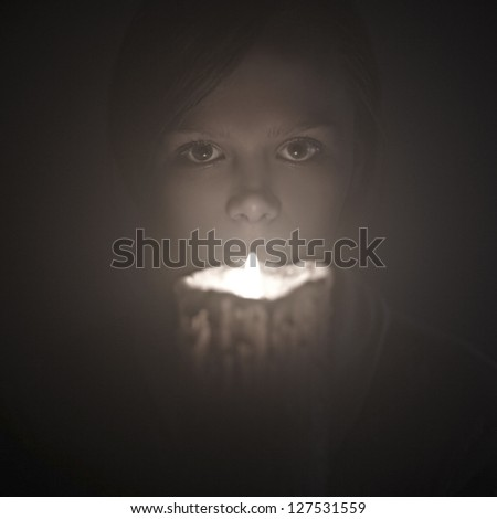 portrait of a beautiful woman with a candle on a black background