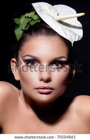 portrait of a beautiful woman with a flower on a dark background - stock photo
