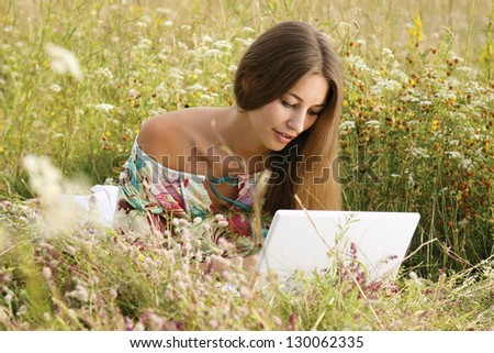 Portrait of a beautiful woman with a laptop lying on the grass