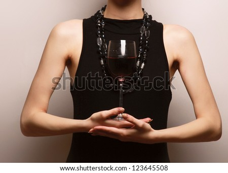 Portrait of a beautiful woman with a wineglass over the wall, isolated on grey