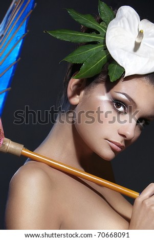 portrait of a beautiful woman with an umbrella and a flower