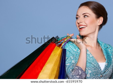 Portrait of a beautiful woman with colored shopping bags isolated on blue