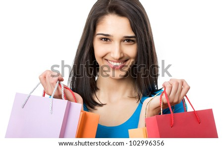 Portrait of a beautiful woman with colored shopping bags isolated on white.