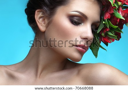 portrait of a beautiful woman with flowers on a blue background