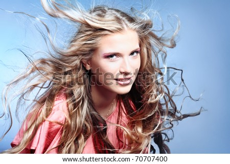 Portrait of a beautiful woman with flying hair. Studio shot over grey background.