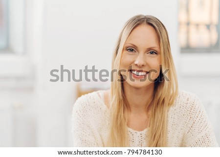 Portrait of a beautiful woman with long blond hair smiling while looking at camera indoors #794784130
