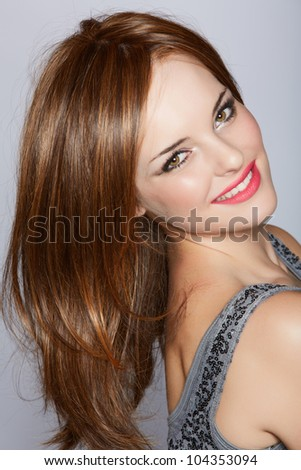 portrait of a beautiful woman with long brown hair looking over her shoulder with a smile over a studio background.