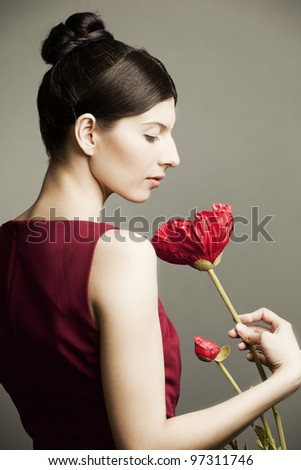 portrait of a beautiful woman with perfect skin and hair in a red dress with a flower on dark background