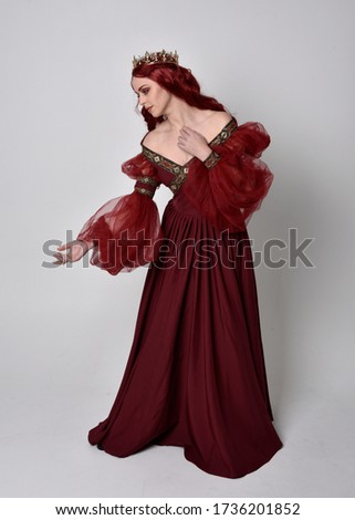 Portrait of a beautiful woman with red hair wearing  a  flowing Burgundy fantasy gown and golden crown.  full length standing pose, isolated against a studio background