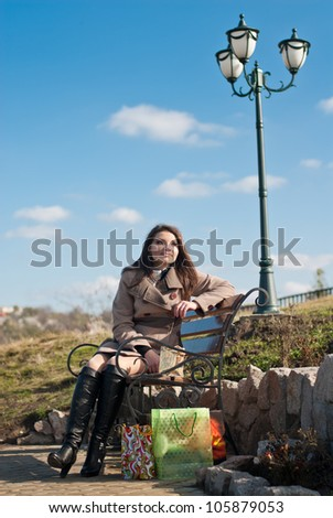 Portrait of a beautiful woman with shopping bags sitting on bench outdoors on a bright sunny day of spring or autumn with blue sky and street lamp on the background with blue sky on the background