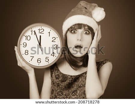 Portrait of a beautiful women with huge clock. Photo in old sepia image style.