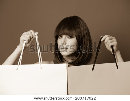 Portrait of a beautiful women with shopping bags. Photo in old sepia image style.