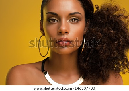 Portrait of a beautiful young African woman wearing gold jewelry. #146387783
