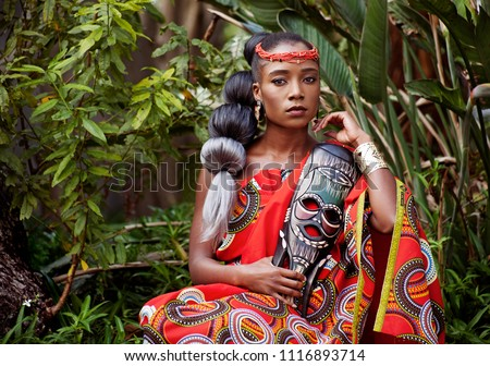 Portrait of a beautiful young African woman wearing traditional clothing and holding a mask while sitting outside with foliage in the background