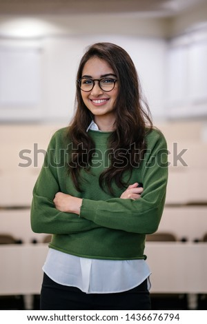 Portrait of a beautiful, young and preppy Indian Asian woman MBA student smiling confidently with her arms crossed in a seminar classroom. She is wearing a preppy outfit and spectacles.