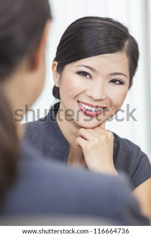 Portrait of a beautiful young Asian Chinese woman or businesswoman in office meeting with female colleague